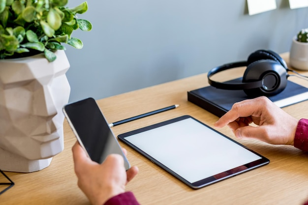 Nowoczesna kompozycja biznesowa w domowym biurze z freelancerem, makiety ekranu tabletu, roślin, notatek, telefonu komórkowego i materiałów biurowych w stylowej koncepcji wystroju domu.