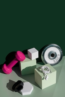 Nowoczesna kompozycja fitness z ciężarami na podium kostki, słuchawkami i inteligentnym zegarkiem na kolorowym bloku szmaragdowo-zielonym i izometrycznym tle miętowym