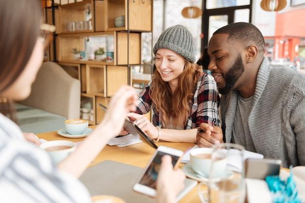 Nowoczesna komunikacja. szczęśliwa ładna rudowłosa dziewczyna trzyma tablet i pokazuje zawartość na jej międzynarodowym koleżance w kawiarni.