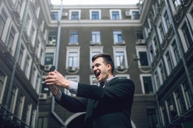 Nowoczesna komunikacja. uliczne selfie dla mediów społecznościowych, szczęśliwa wiadomość dla biznesmena