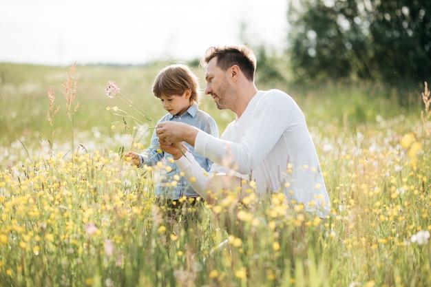 Nowoczesna koncepcja fotografii ojcowskiej, młody tata spędza czas z małym synem na łonie natury