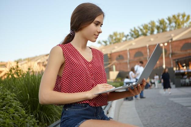 Nowoczesna koncepcja stylu życia, technologii i urządzeń elektronicznych. stylowa młoda kobieta w niebieskich spodenkach dżinsowych i topie z polki siedzi na ławce przy ruchliwej ulicy z otwartym laptopem, korzystając z połączenia internetowego 4g