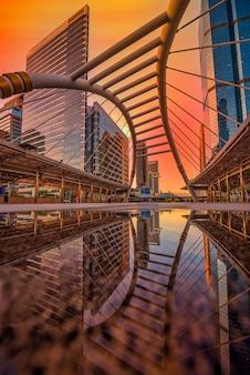 Nowoczesna konstrukcja kształt mostu i budynek o zachodzie słońca w stacji kolejowej, bangkok, tajlandia.