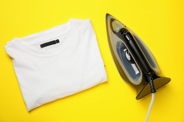 Nowoczesna koszulka z żelaza i składana na żółtym tle, widok z góry