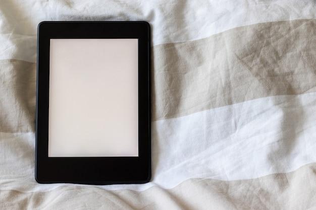 Nowoczesna książka elektroniczna z pustym, pustym ekranem na tkaninie w biało-beżowe paski. makieta tabletu na łóżku. zamknąć widok