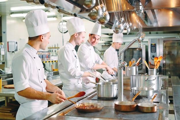 Nowoczesna kuchnia. kucharze przygotowują posiłki na kuchence w kuchni restauracji lub hotelu. ogień w kuchni.