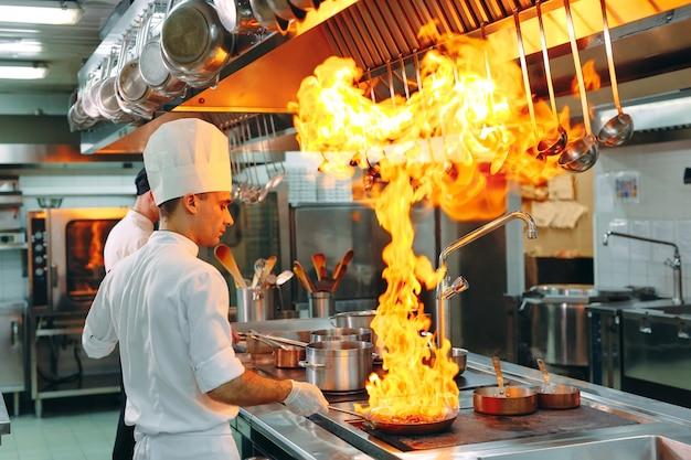 Nowoczesna kuchnia. kucharze przygotowują posiłki na kuchence w kuchni restauracji lub hotelu.
