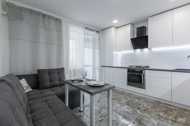 Nowoczesna kuchnia w jasnej tonacji bieli z czarnymi marmurowymi płytkami na podłodze umieszczona w małym mieszkaniu