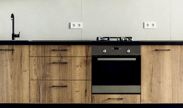 Nowoczesna kuchnia, z bliska, kuchenka gazowa z patelnią, białe i szare minimalistyczne wnętrze.