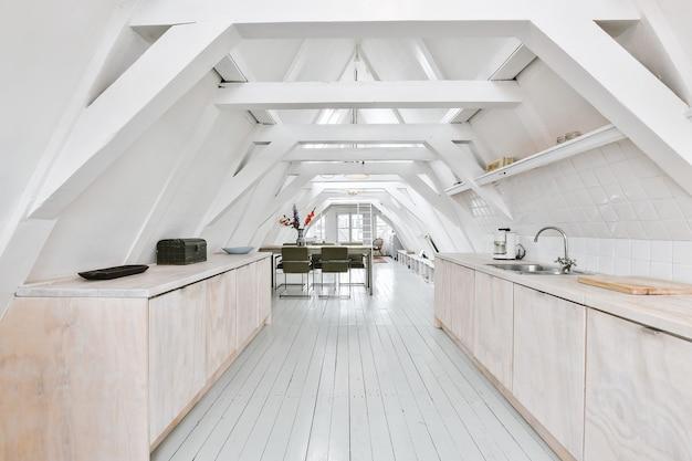 Nowoczesna Kuchnia Z Drewnianymi Szafkami I Minimalistycznym Wystrojem W Mieszkaniu Typu Studio Na Poddaszu Z Białymi ścianami Premium Zdjęcia
