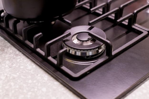 Nowoczesna kuchnia. zbliżenie palników stalowych i czarnej tacy. chromowana płyta kuchenki gazowej. cztery pokrętła sterujące. płyta grzewcza nowej domowej kuchenki gazowej
