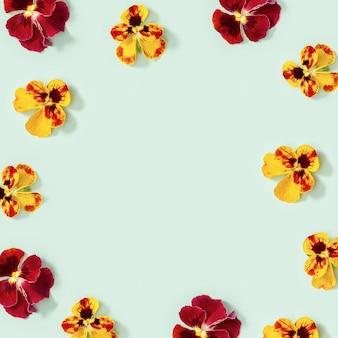 Nowoczesna kwiecista ramka z żółto-czerwonymi kwiatami bratek, małe letnie mieszkanie układane w kwiecistą sezonową stylizację