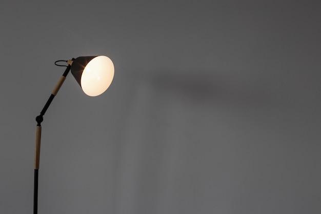 Nowoczesna lampa podłogowa na tle białej ściany