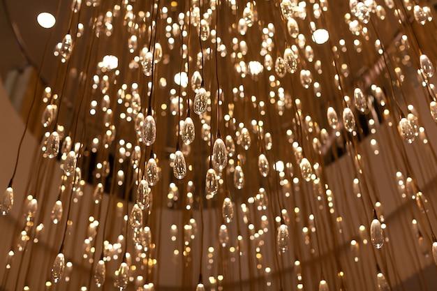 Nowoczesna lampa w postaci licznych szklanych przezroczystych żarówek w kształcie kropli.