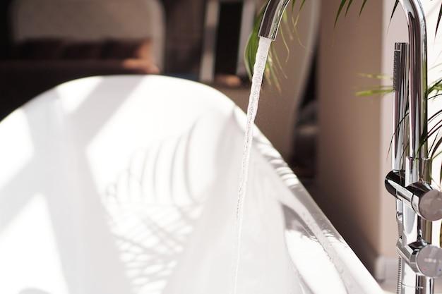 Nowoczesna łazienka. biała wanna z zielonymi gałązkami palmowymi. jasny pokój ze światłem słonecznym z dużego okna. woda wypływa z kranu
