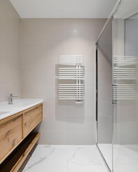 Nowoczesna łazienka z drewnianą podstawą pod grzejnik z białą umywalką do zabiegów ciepłej wody w zimie strefa prysznica ze szklanymi drzwiami łazienka wykończona jasnymi płytkami