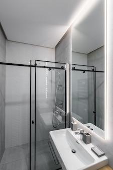 Nowoczesna łazienka z prysznicem w małym mieszkaniu z białymi marmurowymi płytkami