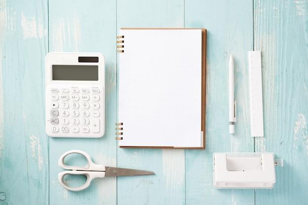 Nowoczesna makieta płaska leżąca notatnik i artykuły papiernicze na niebieskim tle drewnianych - koncepcja kreatywnej przestrzeni do pracy
