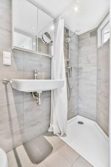 Nowoczesna mała łazienka z szarymi kafelkami z prysznicem w rogu i małą umywalką pod lustrem i lampą