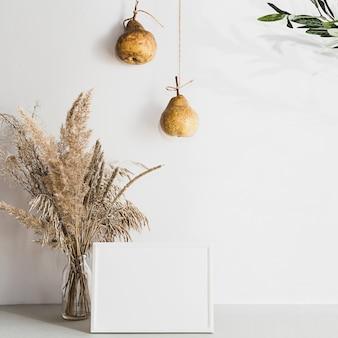 Nowoczesna martwa natura z białą pustą ramką na zdjęcia, trawą pampasową i gruszkami