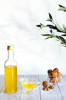 Nowoczesna martwa natura z butelką oleju i szklaną miską z gałązką oliwną orzechów włoskich