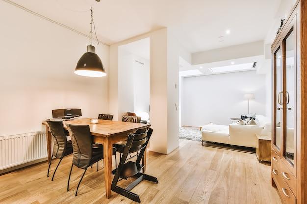 Nowoczesna, minimalistyczna aranżacja wnętrza apartamentu typu studio z otwartą białą kuchnią i strefą jadalną ze stołem i krzesłami oświetloną lampą w stylu loft