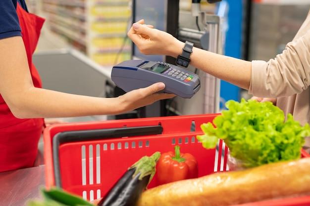 Nowoczesna młoda kobieta korzystająca z technologii inteligentnego zegarka, aby płacić za towary w nowoczesnym supermarkecie