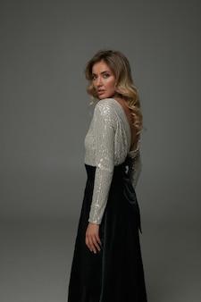 Nowoczesna młoda kobieta w czarnej spódnicy maxi i jedwabnej białej bluzce
