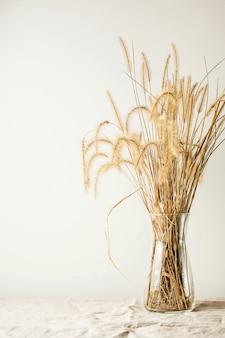 Nowoczesna modna martwa natura z bukietem suszonych kwiatów w szklanym wazonie na drewnianym stole. miejsce na tekst lub reklamy