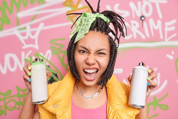 Nowoczesna nastolatka ma dredy wyglądające z bezczelnym wyrazem twarzy w aparacie trzyma dwie butelki z aerozolem do rysowania graffiti, ubrane w modne ubrania