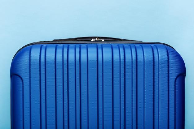 Nowoczesna niebieska walizka na niebieskim tle z bliska z miejsca kopiowania tekstu. koncepcja podróży w stylu minimalistycznym. wakacyjna podróż..