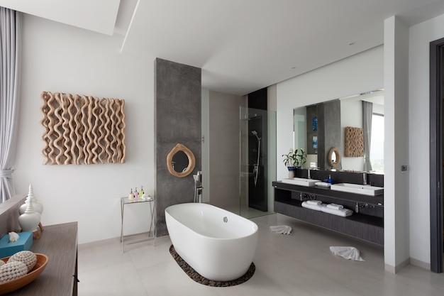 Nowoczesna nowa aranżacja wnętrza łazienki z białą kamienną wanną w nowej willi lub hotelu nowoczesny budynek.