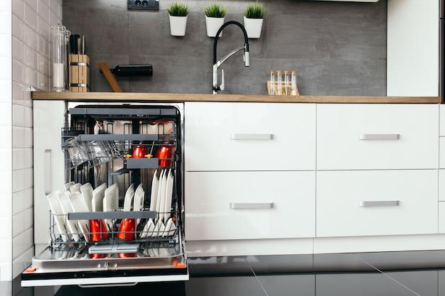 Nowoczesna otwarta zmywarka z czystymi naczyniami w białej kuchni.