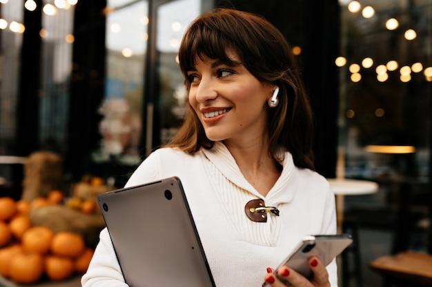Nowoczesna pewna siebie kobieta o brązowych włosach z laptopem