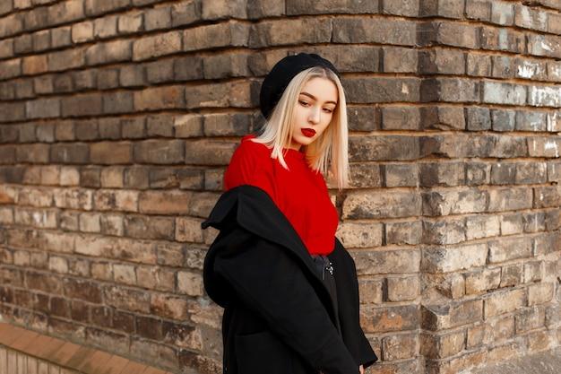 Nowoczesna piękna młoda kobieta blondynka z czerwonymi ustami w luksusowym długim czarnym płaszczu w berecie w czerwonej koszuli w stylowych spodniach stoi w pobliżu ceglanego budynku w jesienny dzień
