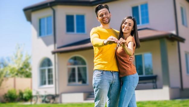Nowoczesna piękna podekscytowana młoda para zakochana stojąca przed nowym dużym domem z kluczami w rękach i przytulająca się podczas świętowania tego zakupu