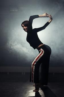 Nowoczesna piękna tancerka w czarnych ubraniach pozowanie przed studio w dym