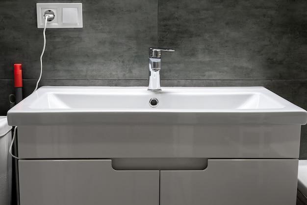 Nowoczesna prostokątna umywalka z chromowaną metalową baterią w stylowej łazience z szarą betonową ścianą