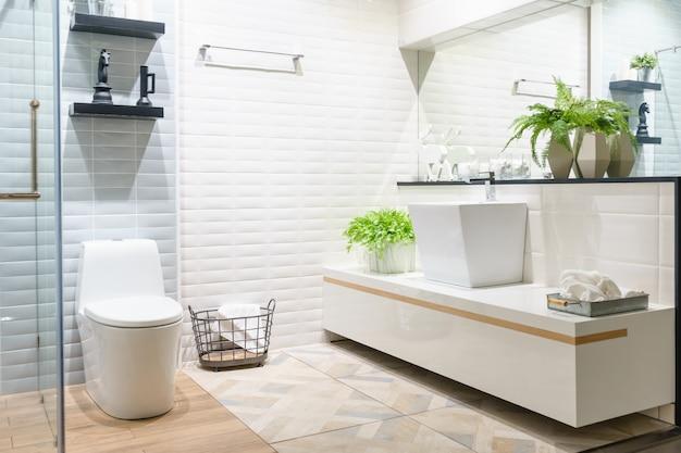 Nowoczesna przestronna łazienka z jasnymi kafelkami z wc i umywalką. widok z boku