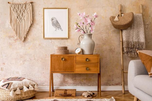 Nowoczesna retro kompozycja salonu z drewnianą komodą vintage, sofą, rattanową pufą, drabiną, makramą, dywanem, poduszką, złotą ramą, kwiatami, dekoracją i akcesoriami osobistymi.