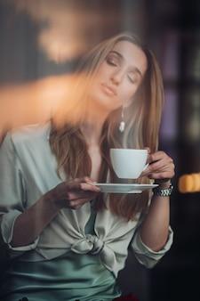Nowoczesna romantyczna piękna młoda dziewczyna ciesząca się zapachem filiżanki kawy z zamkniętymi oczami podczas relaksu w kawiarni w pomieszczeniu