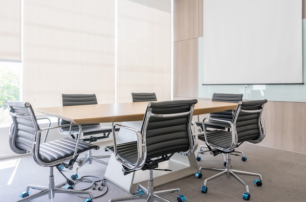 Nowoczesna sala konferencyjna z ekranem projekcyjnym i stołem konferencyjnym