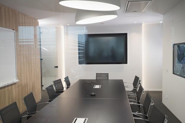 Nowoczesna sala spotkań biznesowych z fotelami i biurkiem