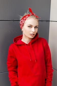 Nowoczesna śliczna młoda kobieta z naturalnym makijażem i blond włosami w amerykańskiej czerwonej bandanie w modnej bluzie z kapturem pozuje w pobliżu szarej ściany w stylu vintage w mieście