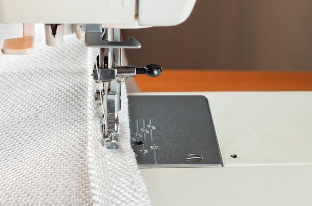 Nowoczesna stopka dociskowa do maszyn do szycia. proces szycia ozdobnego obramowania z białej tkaniny.