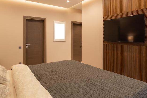 Nowoczesna sypialnia w mieszkaniu, w neutralnych kolorach ziemi. podwójne łóżko.