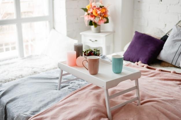 Nowoczesna sypialnia w pastelowych kolorach. kawa i truskawki na małym stole zdobiły świece.