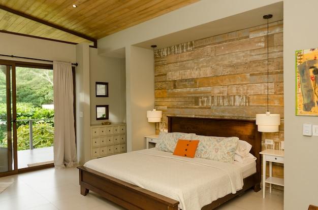 Nowoczesna sypialnia, wzorzyste poduszki, lampa, okna