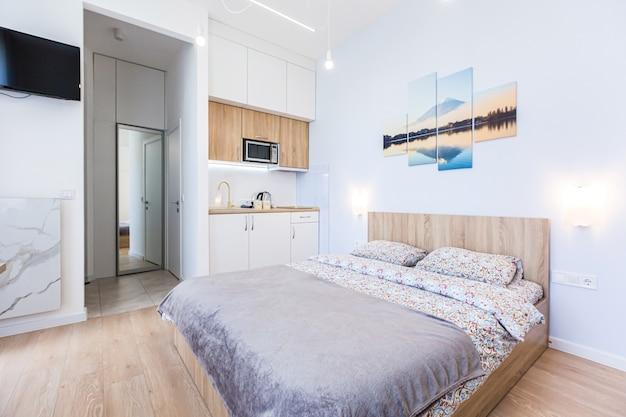Nowoczesna sypialnia z dużym stylowym łóżkiem i małą kuchnią