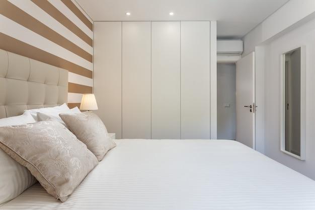 Nowoczesna sypialnia z poduszkami i łóżkiem dla turystów.